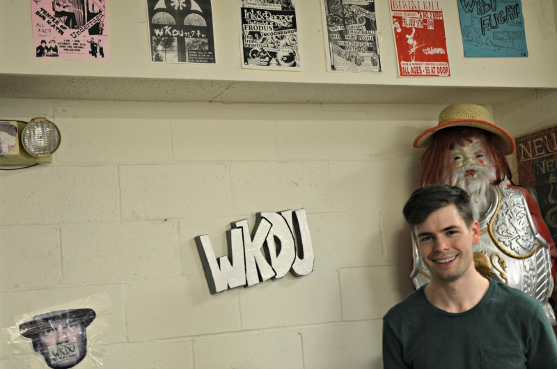 Senior communications major and WKDU DJ Nick Stropko stands in front of old WKDU concert posters in the college radio station's studio.