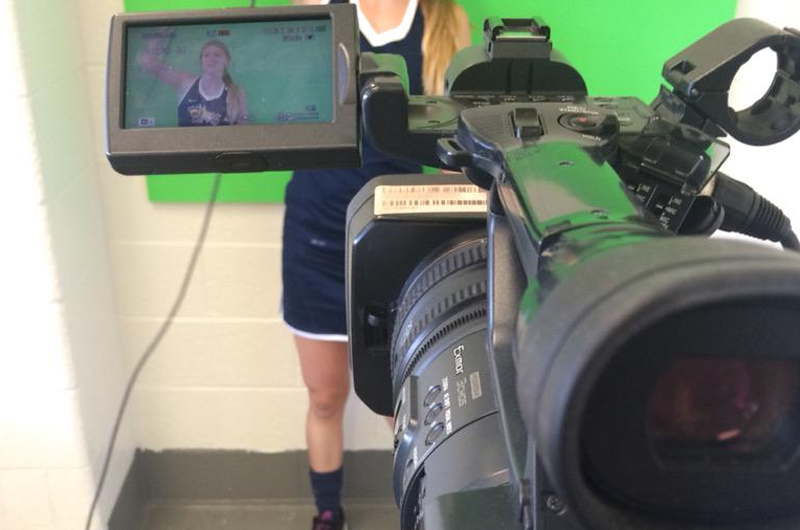 A member of the Women's field hockey team doing a video.