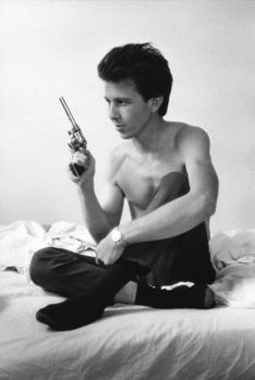 A shirtless man holding a revolver.