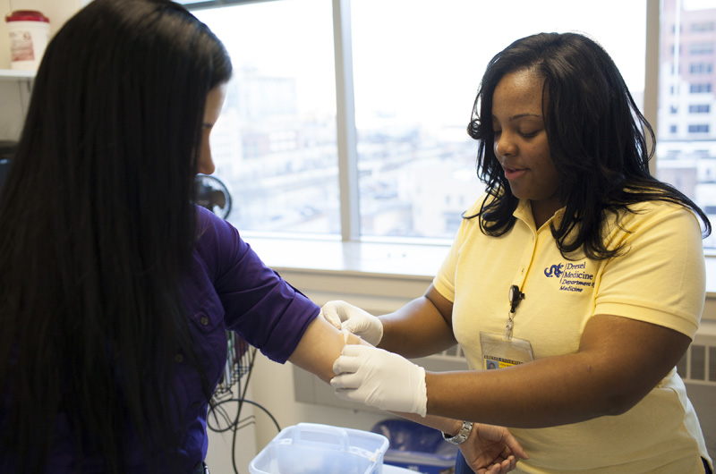 Myna Whitney working with a patient in her job as a medical assistant in the Drexel College of Medicine.