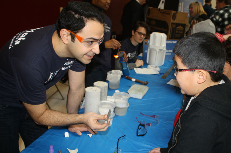 Current Drexel post-doctoral researcher, then PhD candidate Babak Anasori gives a one-on-one materials science demonstration to an interested young boy.