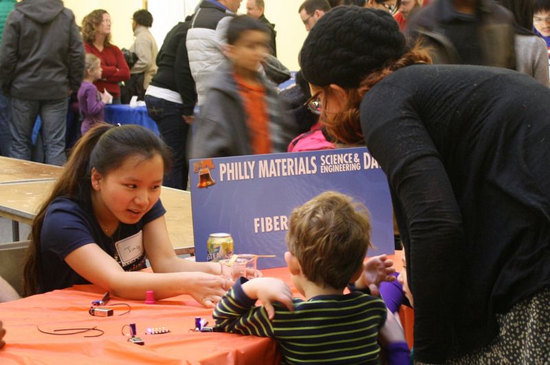 Drexel student Jing Chen demonstrates fiber optics to a young participant at the 5th annual Philly Materials Science and Engineering Day.