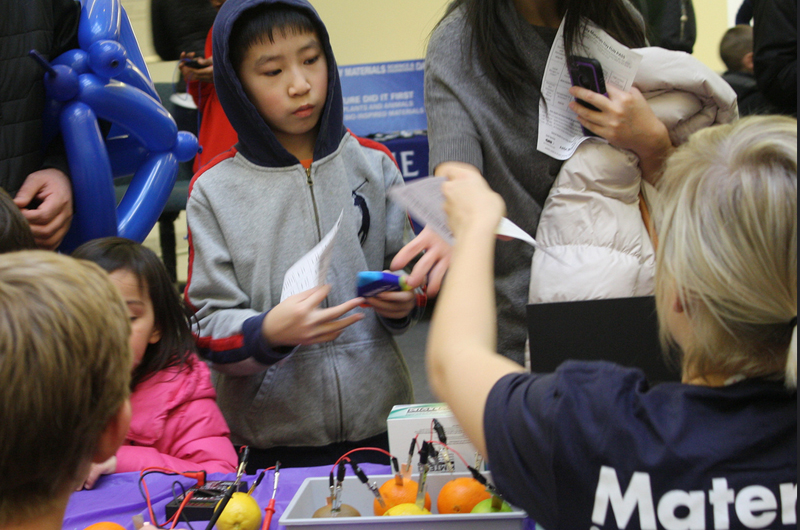 Young boy learns about making batteries from fruit from Drexel materials science students.