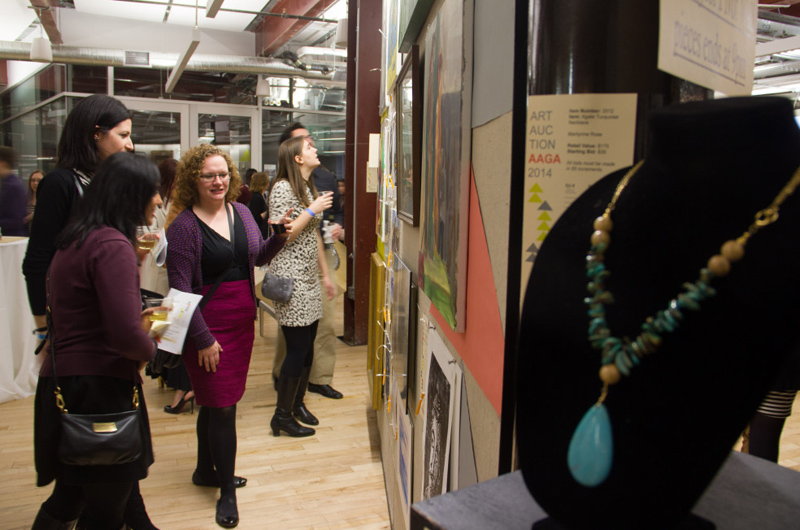 Attendees at last year's art auction looking over some of the available pieces.
