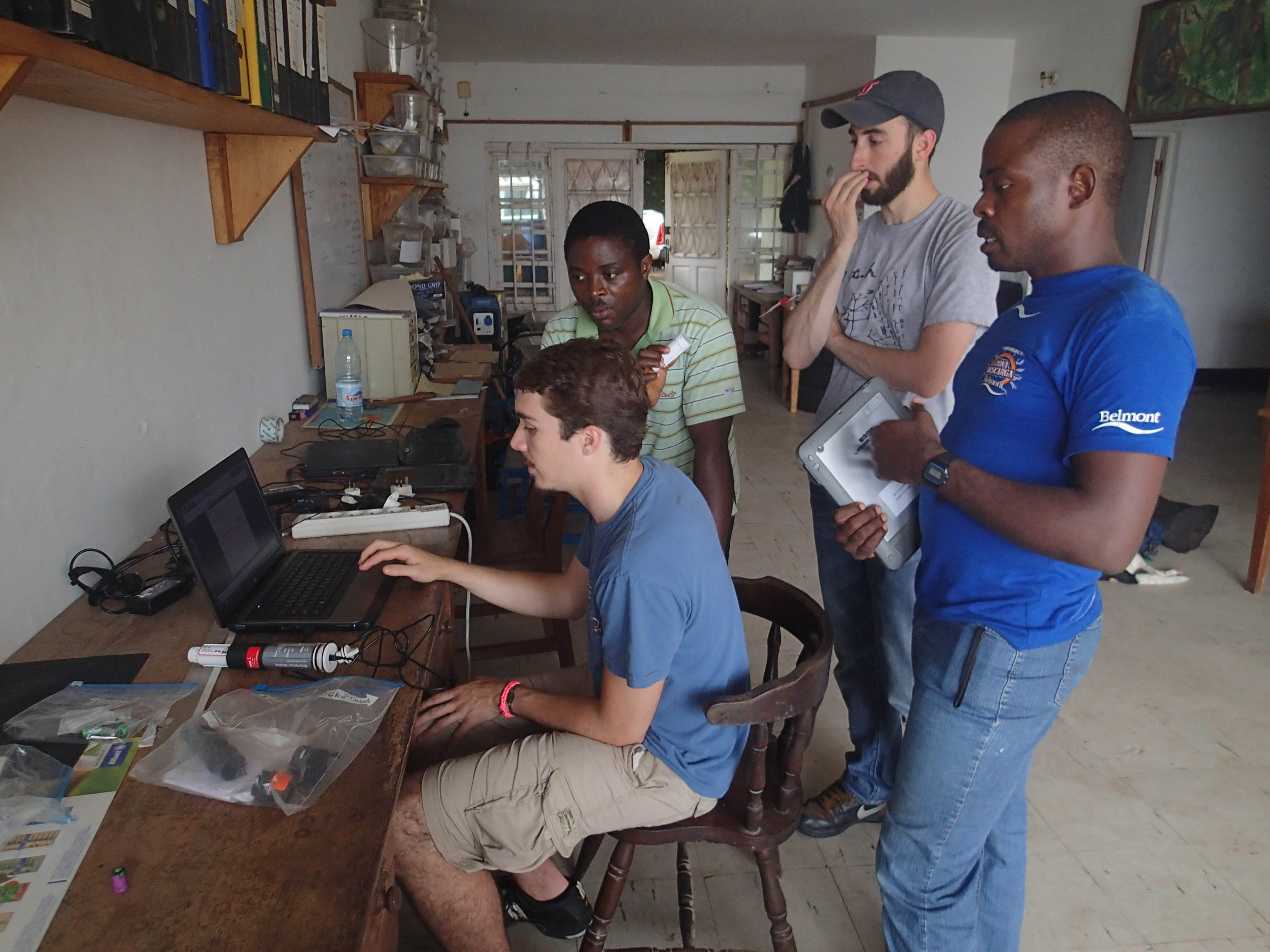 Drexel University researchers Paul Sesink Clee (seated) and Matthew Mitchell (standing, center) analyzing climate data from a field site with researchers from Ebo Forest Research Project. Credit Mary Katherine Gonder