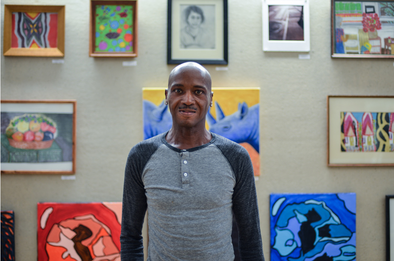 Project HOME alumnus Gerald Halley stands in front of his artwork.