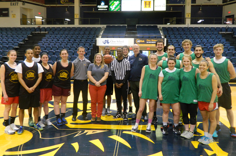 Before the intramural basketball coed championship, Drexel Director of Athletics Eric Zillmer (center, in blue shirt and glasses) was honored for his work.