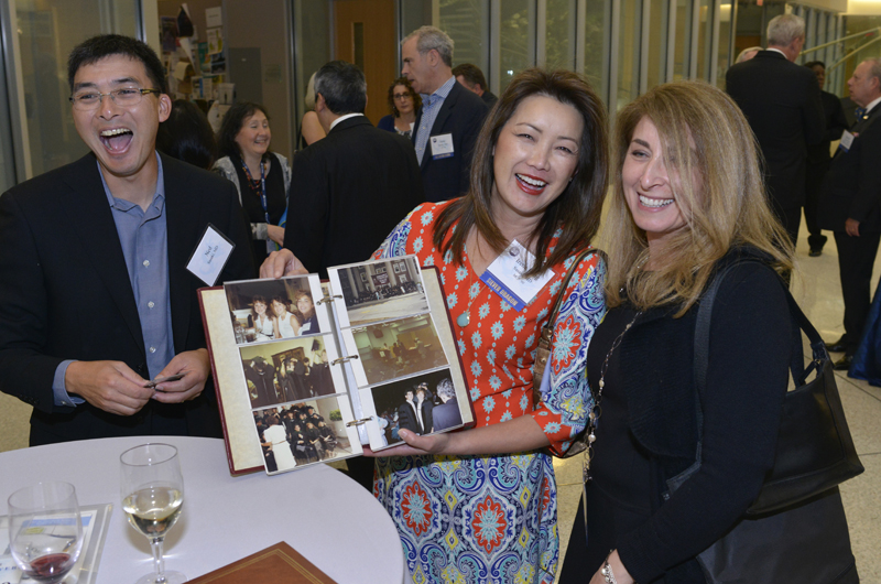 Silver Dragons (those who graduated 25 years ago) flip through old photos at their 25-year reunion reception.