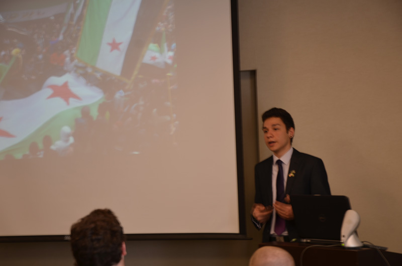 Hallak discussing demonstrations in Syria with a photo of one from his presentation flanking him.