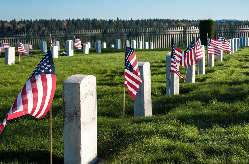 Graves of veterans decorated with flags.