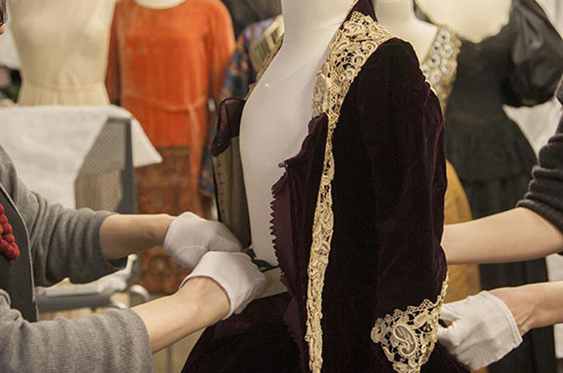 Working on a mannequin for Immortal Beauty: Highlights from the Robert and Penny Fox Historic Costume Collection. Photo by Michael J. Shepherd.
