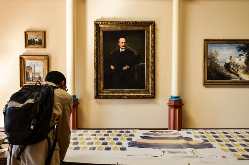 A student writing out his wishes for his time at Drexel on a banner decorated with cakes before a portrait of the University's founder, Anthony J. Drexel. Photo by Ola Baldych.