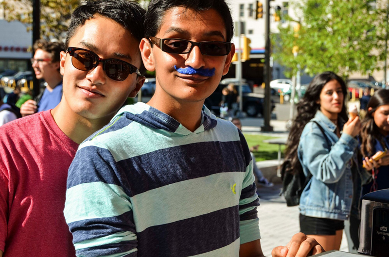 A pair of students waiting for ice cream, one taking advantage of the mustaches made available to students. Photo by Ola Baldych.