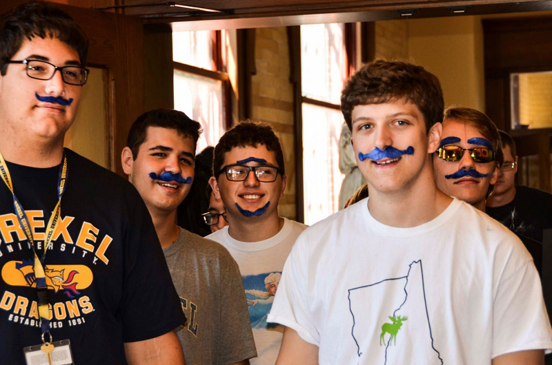 A group of students sporting A.J. Drexel mustaches in Drexel blue. Photo by Ola Baldych.