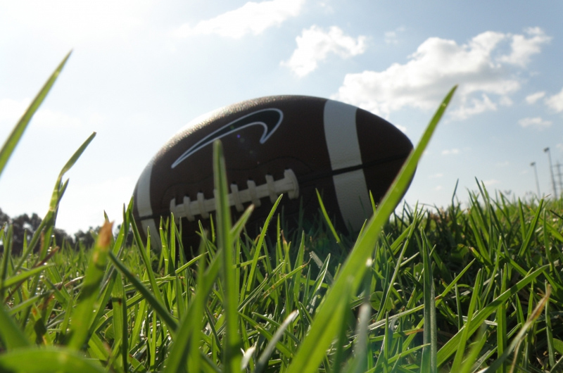 A football laying in the grass. Photo by RonAlmog (https://www.flickr.com/photos/ronalmog/3104856676/).