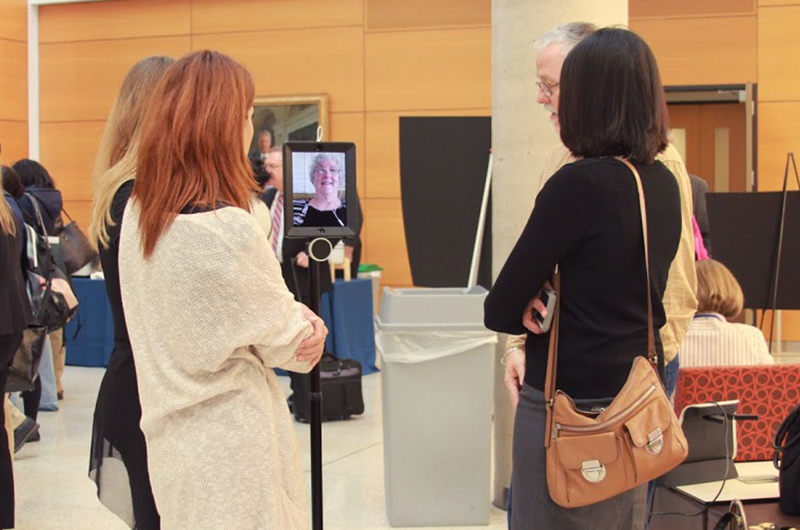 Attendees at the third Collaboratory event chat with Karyn Holt via a robot.