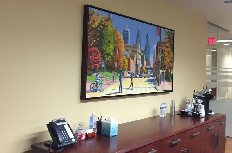 The conference room at Drucker & Scaccetti's Center City office features a painting of Drexel's campus. Employees of all levels, including interns, are Drexel Dragons.