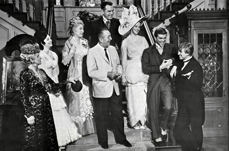 "Walt Disney, center, photographed with the cast of ""The Happiest Millionaire"" on set. Fred MacMurray, who portrayed the titular character and Anthony J. Drexel's grandson, stands behind him."