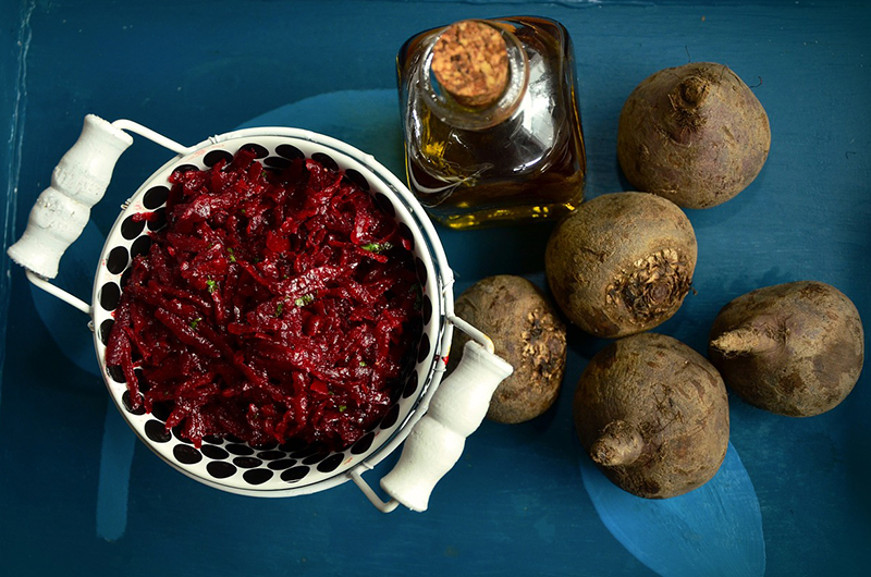 A bowl of red shredded beets, next to dirty whole beets on a blue table.