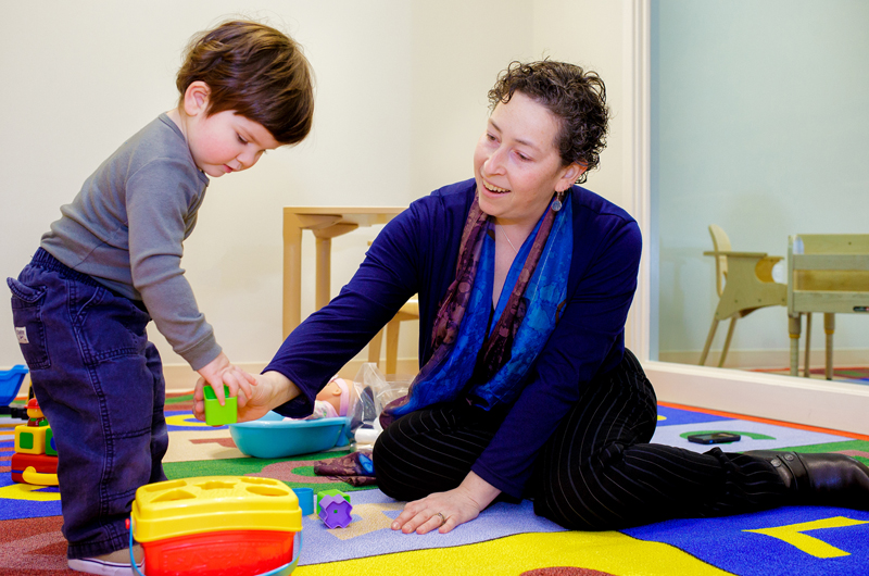 Diana Robins, PhD, of the A.J. Drexel Autism Institute, plays with a toddler who is in the age range that she believes all children should be screened for autism spectrum disorder. Photo by Jeff Fusco.