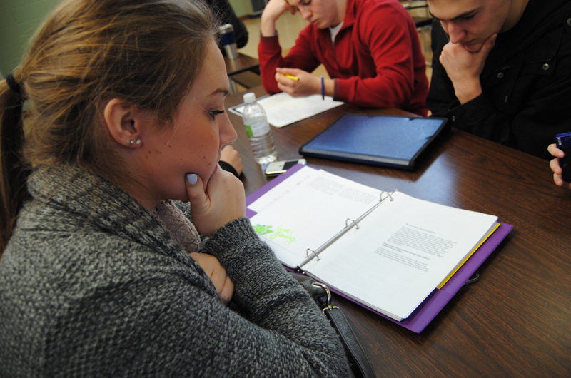 Students studying from binders at a table.