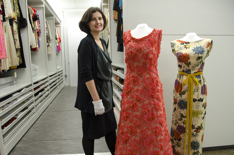 Clare Sauro, curator of the Fox Historic Costume Collection, stands next to a coral-encrusted Hubert de Givenchy couture gown worn by Grace Kelly.