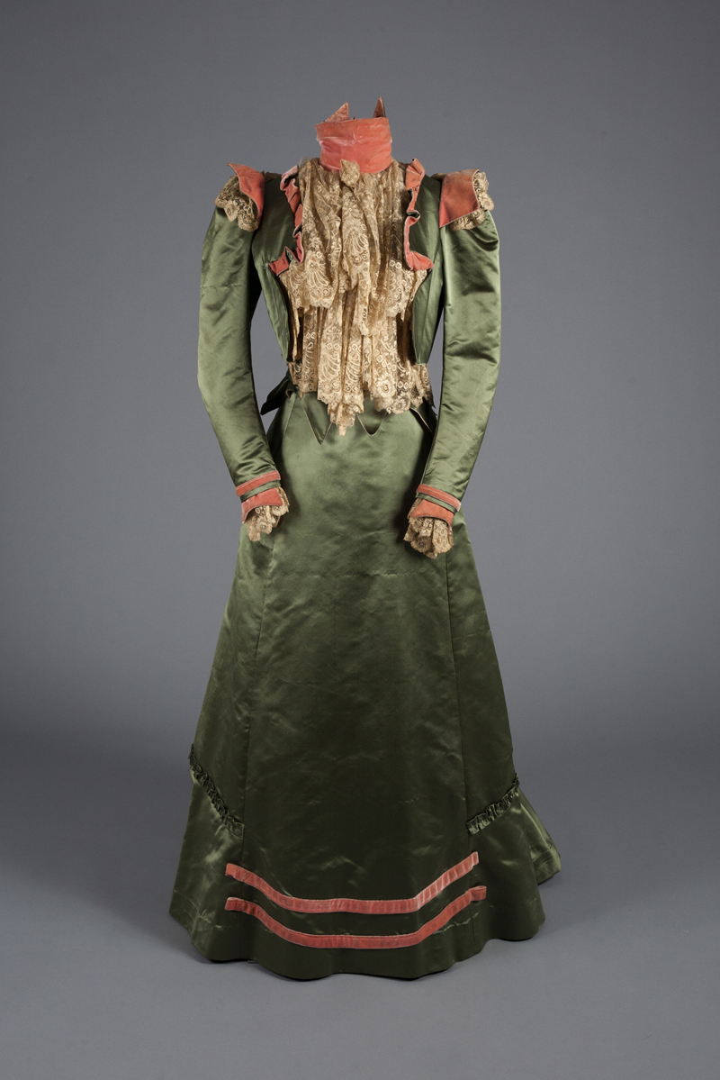 A green satin, pink velvet and lace walking dress from 1900. Gift of Mrs. James Creese.