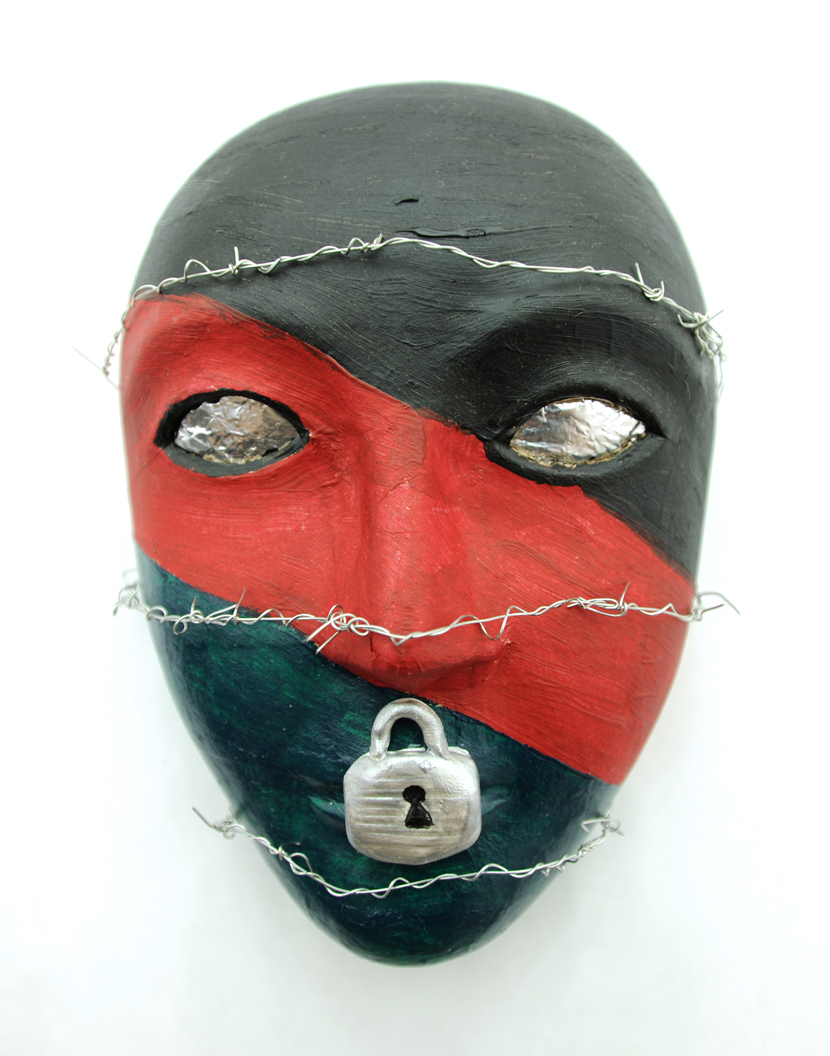 A red and black mask with a lock over the lips and razor wire wrapped around the face. One of the masks created by a U.S. military service member as part of an art therapy program being analyzed by Girija Kamal, of Drexel's College of Nursing and Health Professions.