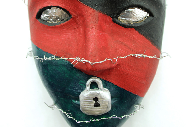 A red and black mask featuring a lock over the mouth and razor wire. One of the masks created through the art therapy program at Walter Reed National Military Medical Center that has partnered with Drexel College of Nursing and Health Professions.