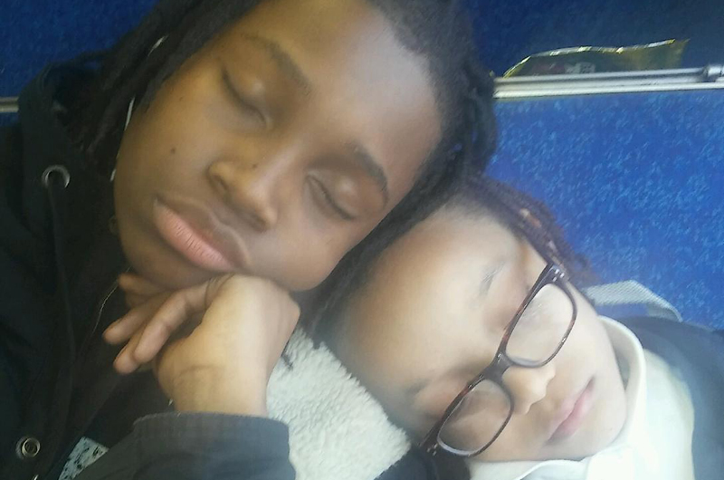 "A photo of two boys with their heads together sleeping. Taken by Angela S. of the Philadelphia Witnesses to Hunger, she said, ""To get a good education, my sons have to take two buses and a train through the 'hood to get to school. They fight all day, but here they were tired, cold, and supporting each other just trying to get home safe."""