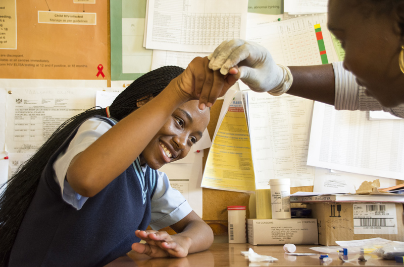 A young girl holding her finger out for an HIV test.