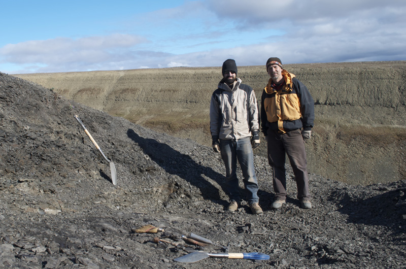 Jason Downs and Ted Daeschler side by side at the dig site with their tools.