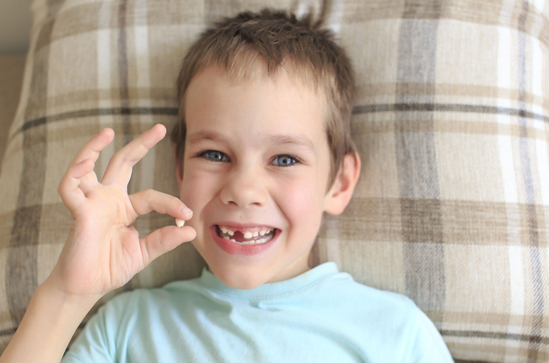 A child holding up one of his baby teeth.