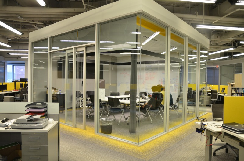The lab's conference room is surrounded by glass walls in the middle of the student workstations.