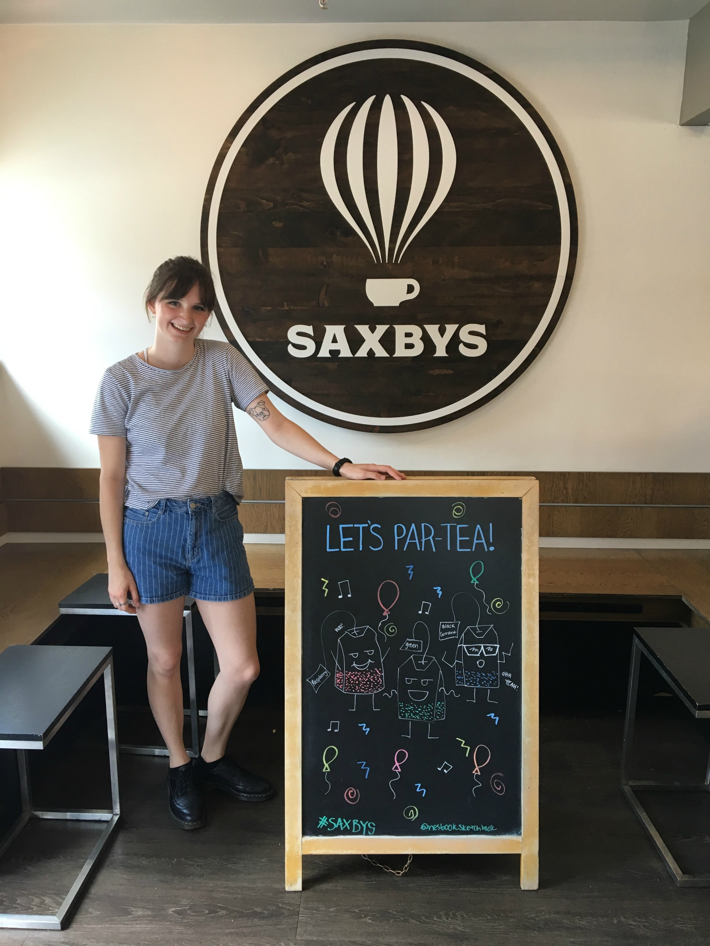 Graphic design major Abbey Nesbitt poses with one of the Saxbys chalkboard signs displaying her art.