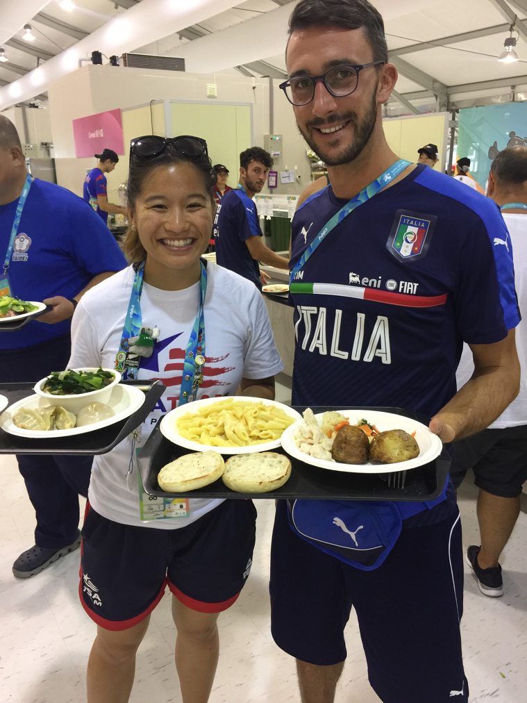 Drexel nutrition intern Leah Tsui checking out the stacked carbohydrate plate of a member of the Italian men's soccer team at the athletes village dining hall.