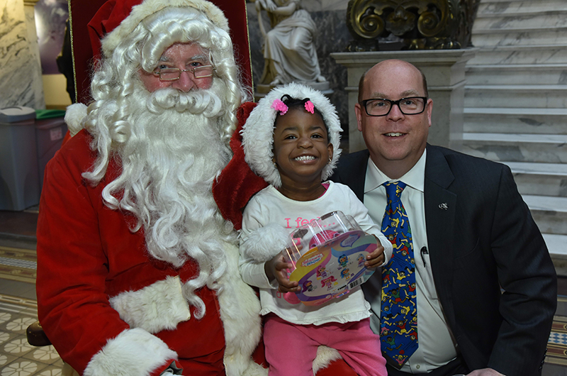 Santa Claus and Office of Government and Community Relations Senior Vice President Brian Keech met with a very excited member of the community at the Dec. 11 toy distribution ceremony.