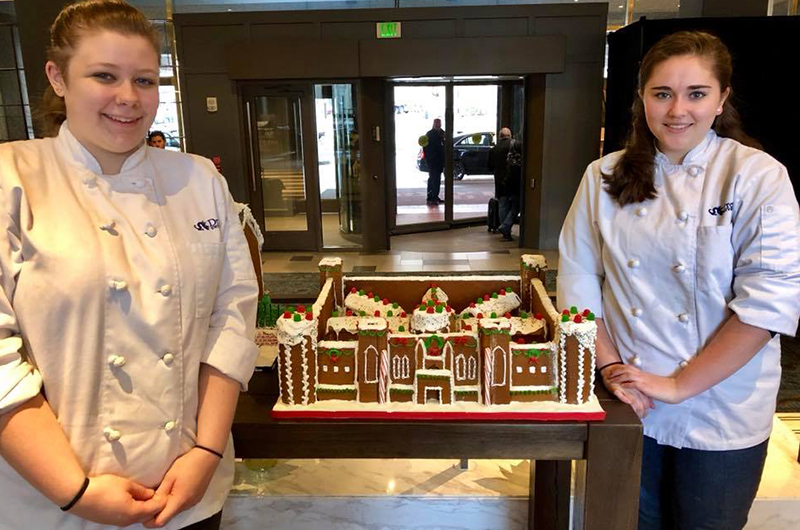 Melissa Martin, left, and Katelyn Comerford stand with the finished Eastern State Penitentiary gingerbread house at the Logan Hotel.