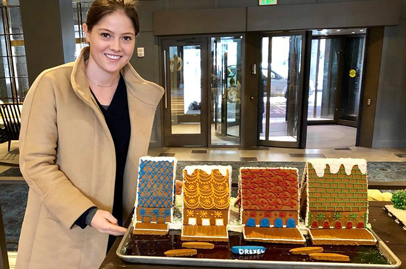 Nora Vaughan stands with the finished Boathouse Row gingerbread house display at the Logan Hotel.