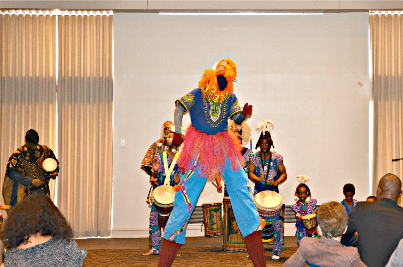 A faceless stilt-walker performs with the Universal African Drum and Dance Ensemble.