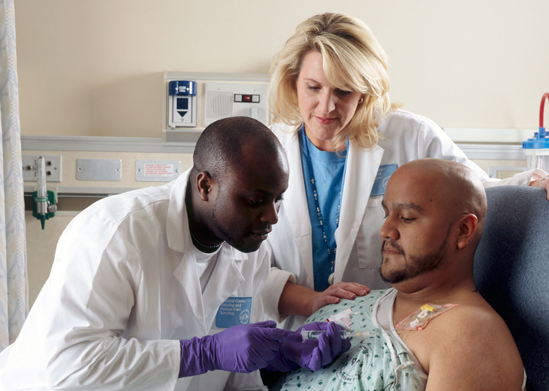 A pair of doctors treating a patient with chemotherapy.