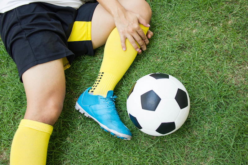 Injured soccer play holds knee on field.