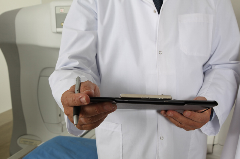 A doctor in a white coat holding a clipboard