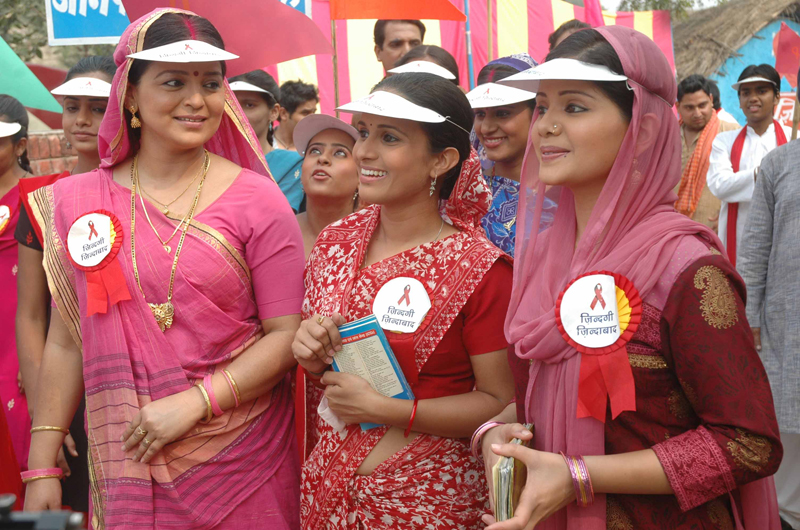 A group of women wearing visors and buttons with red ribbons for HIV awareness.
