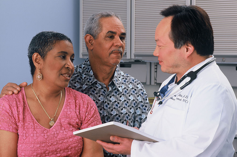 A Latino couple visiting with a physician.