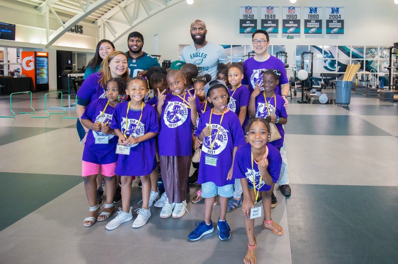 ExCITe Center Director Youngmoo Kim, Eagles safety Malcolm Jenkins and a group of Young Dragons pose in the team's weight room.