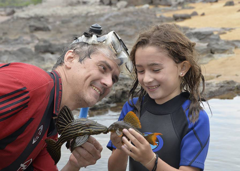 Mark Sabaj and his daughter Sofia holding fish