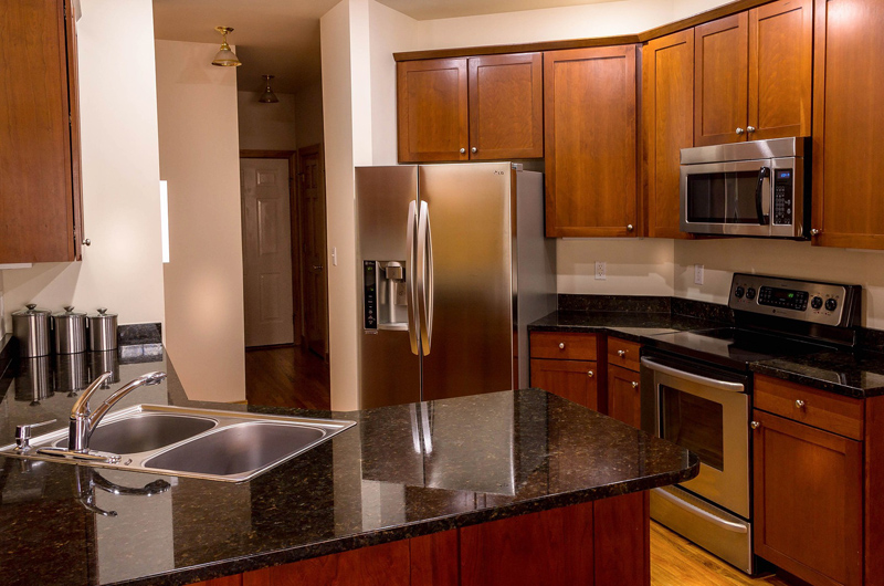 Kitchen with black countertops, sink, oven, microwave and refrigerator.