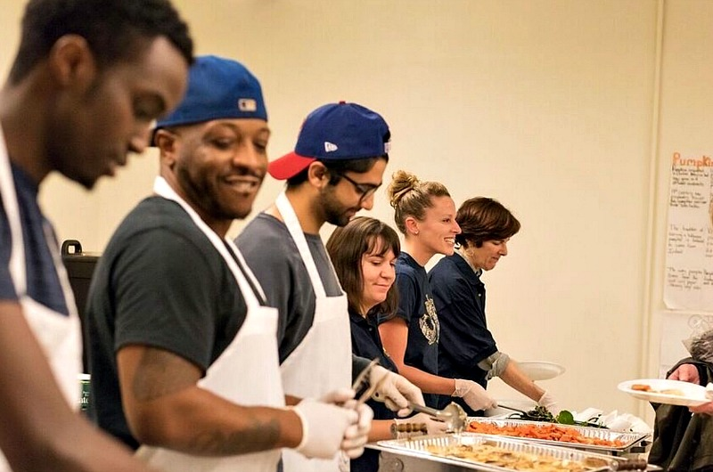 Institutional Advancement staff members Michelle Crouch, Gina Kerwin and Wendy Univer work alongside Drexel students to serve dinner to guests at the Dornsife Community Dinner on Dec. 6, 2016.