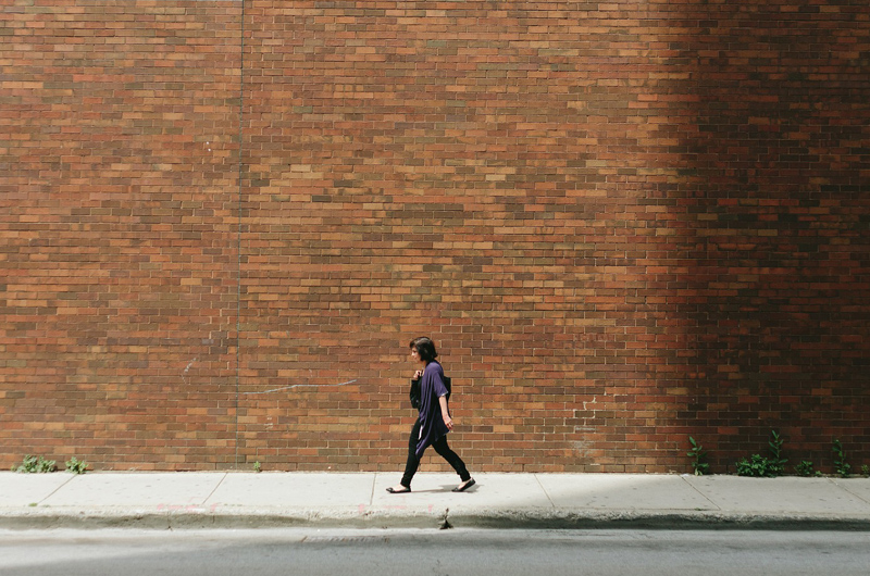 A woman walking on a sidewalk in front of a brick wall.